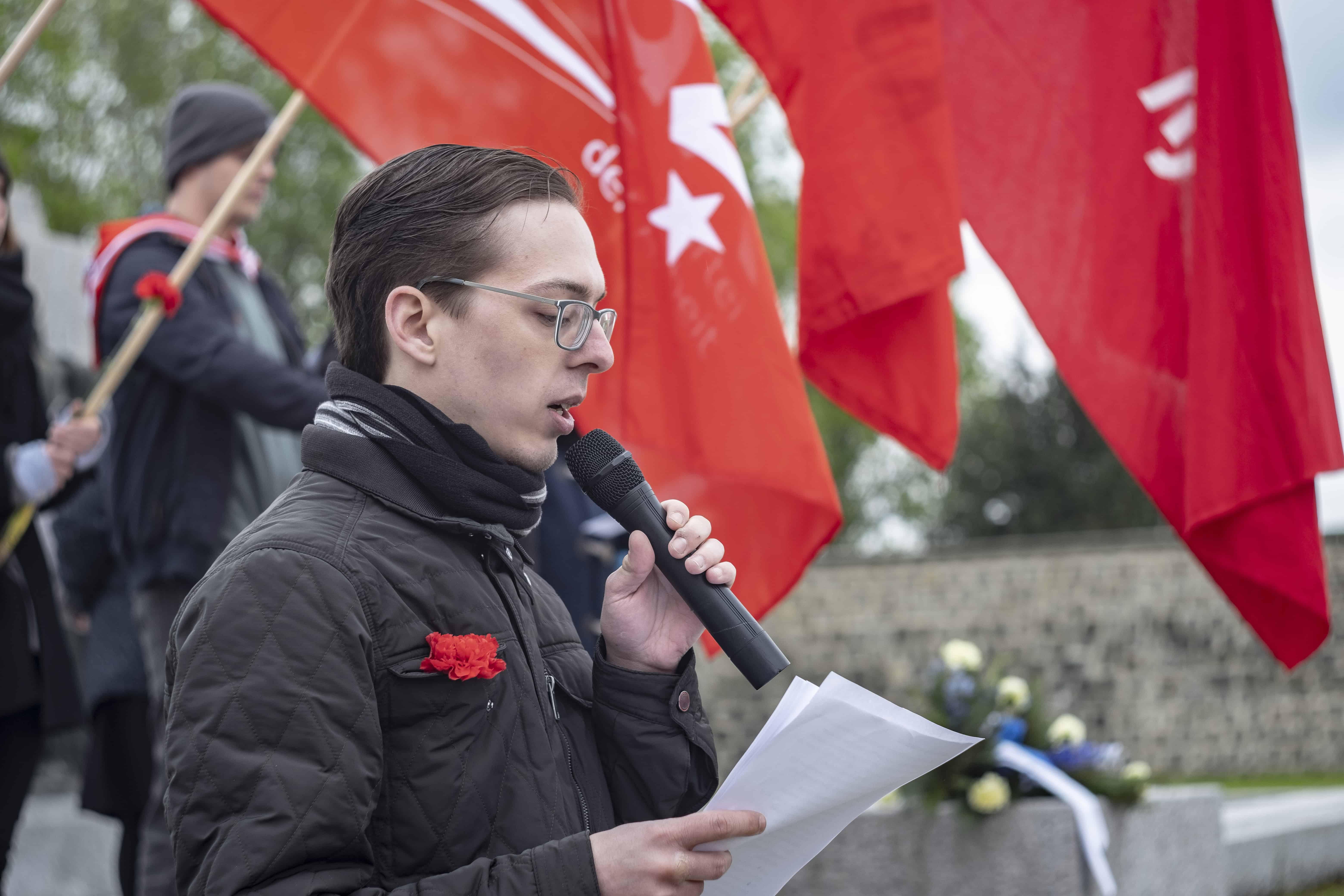 Redner vorne und im Hintergrund rote Fahnen